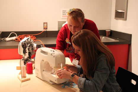 Crystal (Maker Corps 2013) assists with a sewing machine during Maker Educator Boot Camp. Along with children, families, and youth, MAKESHOP holds events for educators, to help them grow skills and approaches that they can take back to their schools, libraries and community centers.