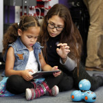 Jayla Bryan-Smith, 7, and Montana Manalo of Americorps, play with an iPad-controlled robotics device at Brentwood School in East Palo Alto, Calif., where students showed off their Makerspace classroom on Monday, May 15, 2015. The classroom is outfitted with laptops and printers donated by Facebook in an initiative to provide students with STEM opportunities. (Karl Mondon/Bay Area News Group)