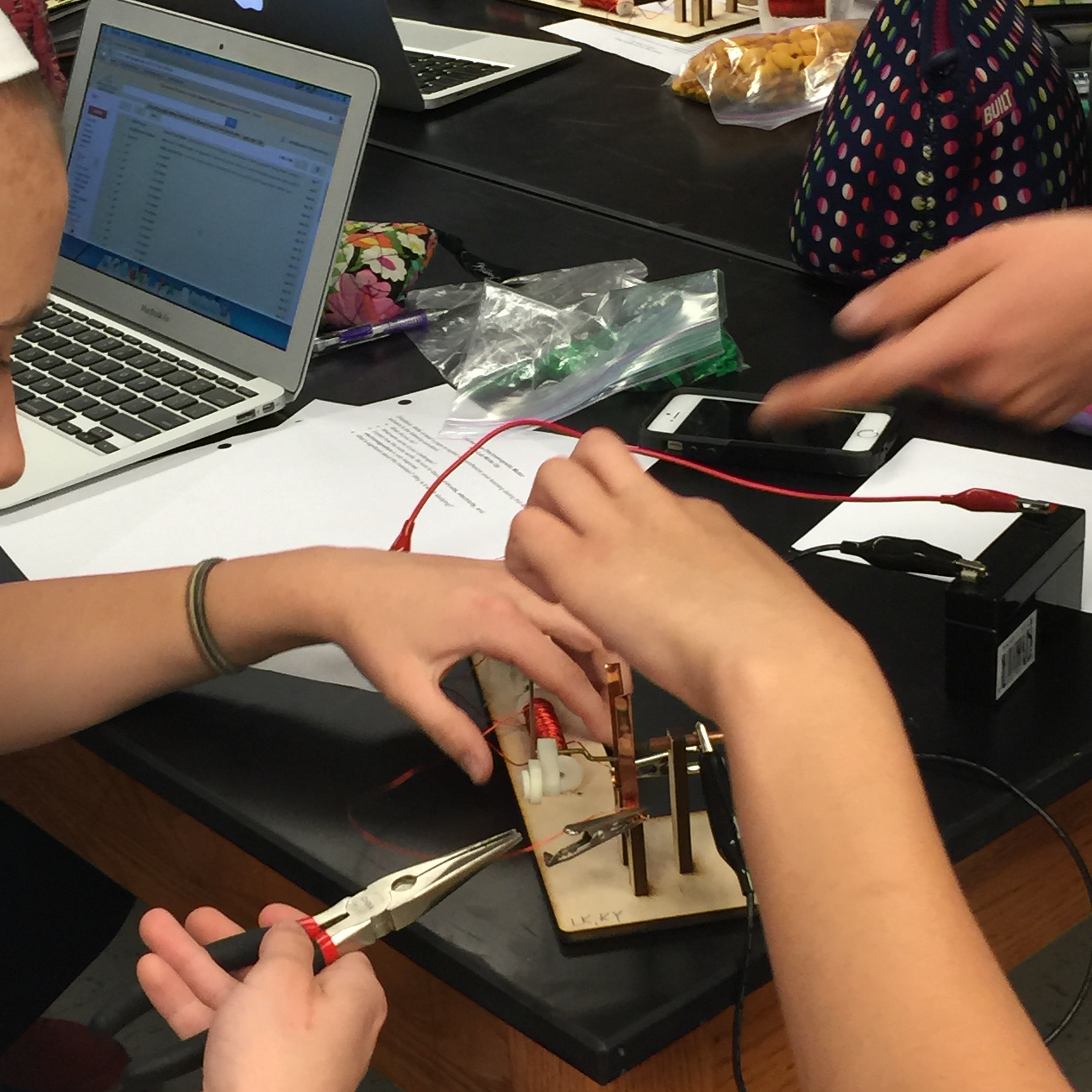Two students' hands working on a circuit project together. Image courtesy of Pam Moran.