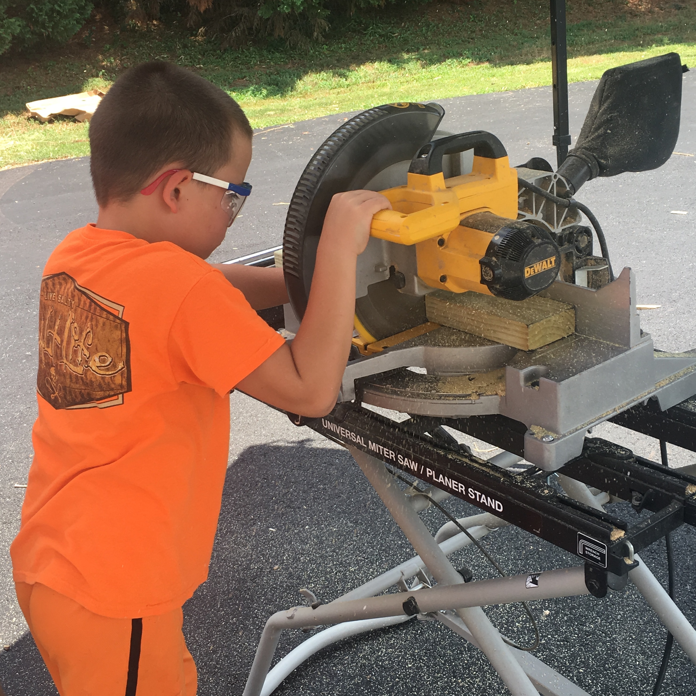A young boy at Albemarle County Public Schools in an orange shirt and shorts uses a miter saw