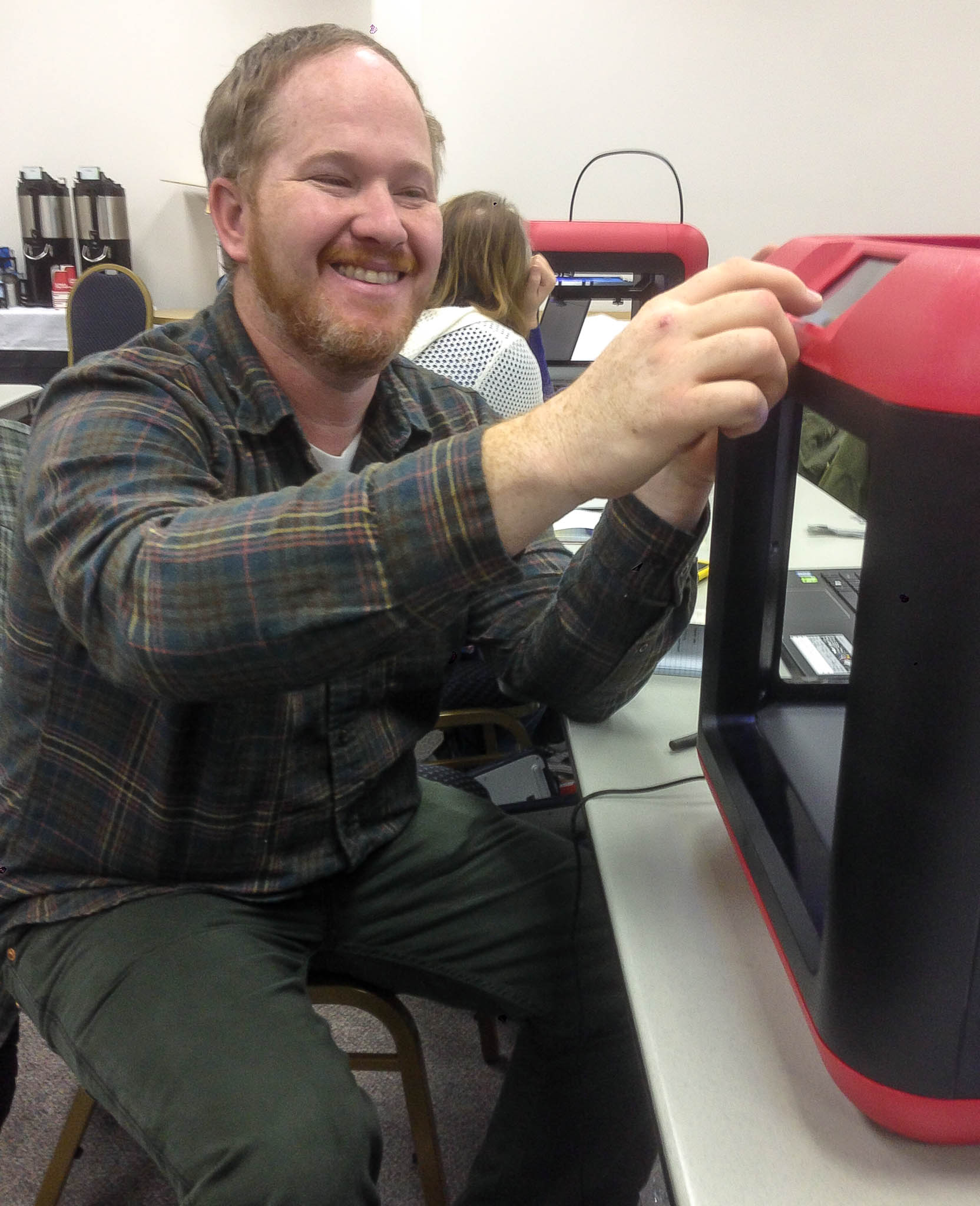 A photo of a white man with a reddish beard smiling. He is seated next to a red and black MakerBot 3D printer.