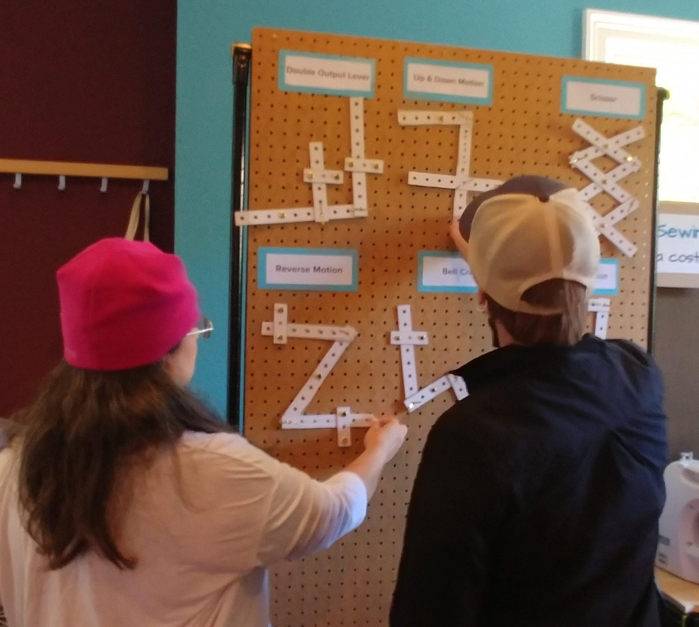 Two women, workshop attendees, stand in front of a pegboard with examples of various types of cardboard linkages.