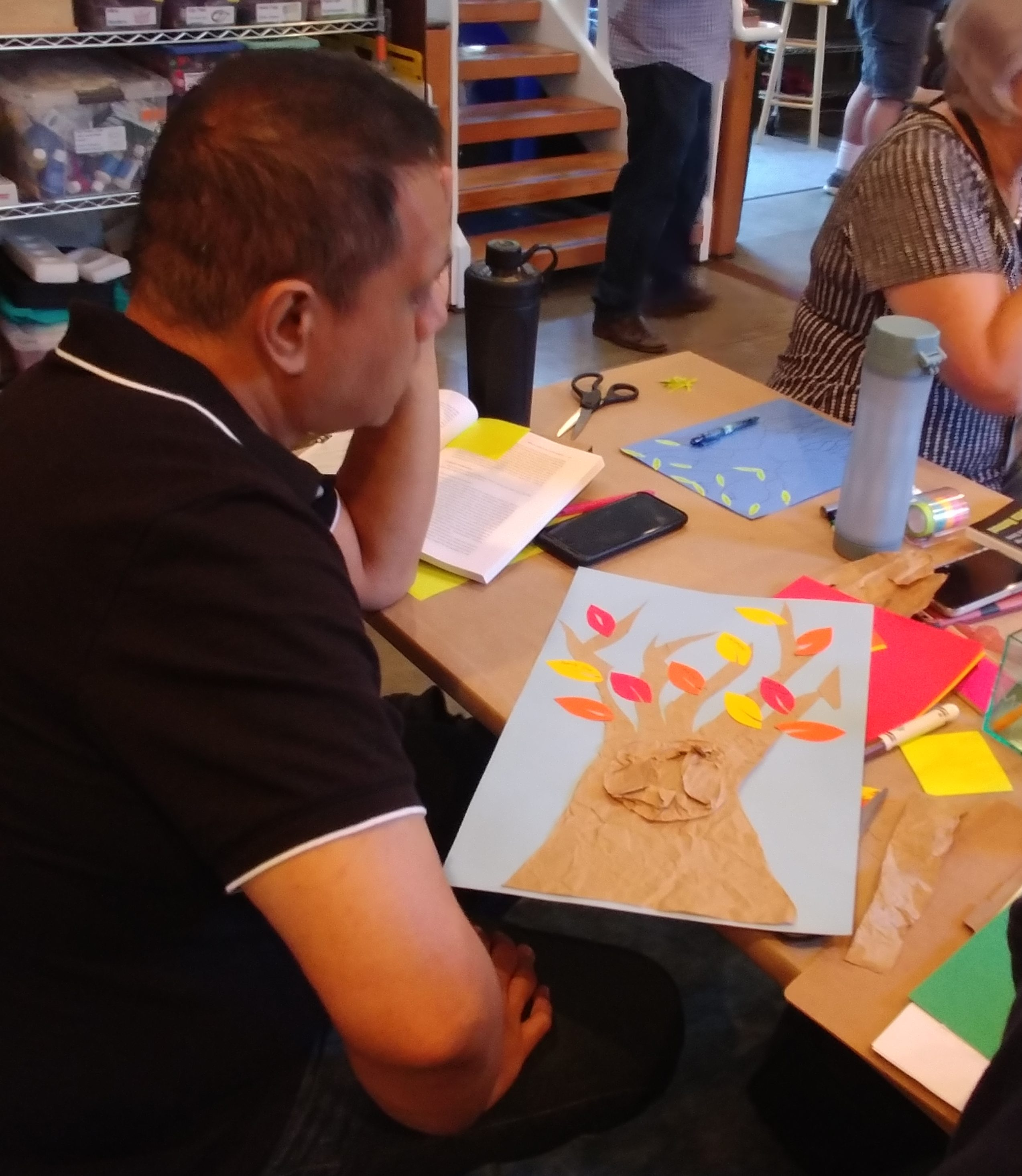 Elson, a male workshop attendee, contemplates his culture tree. His tree is made of brown paper with yellow, red, and orange leaves on a blue background.