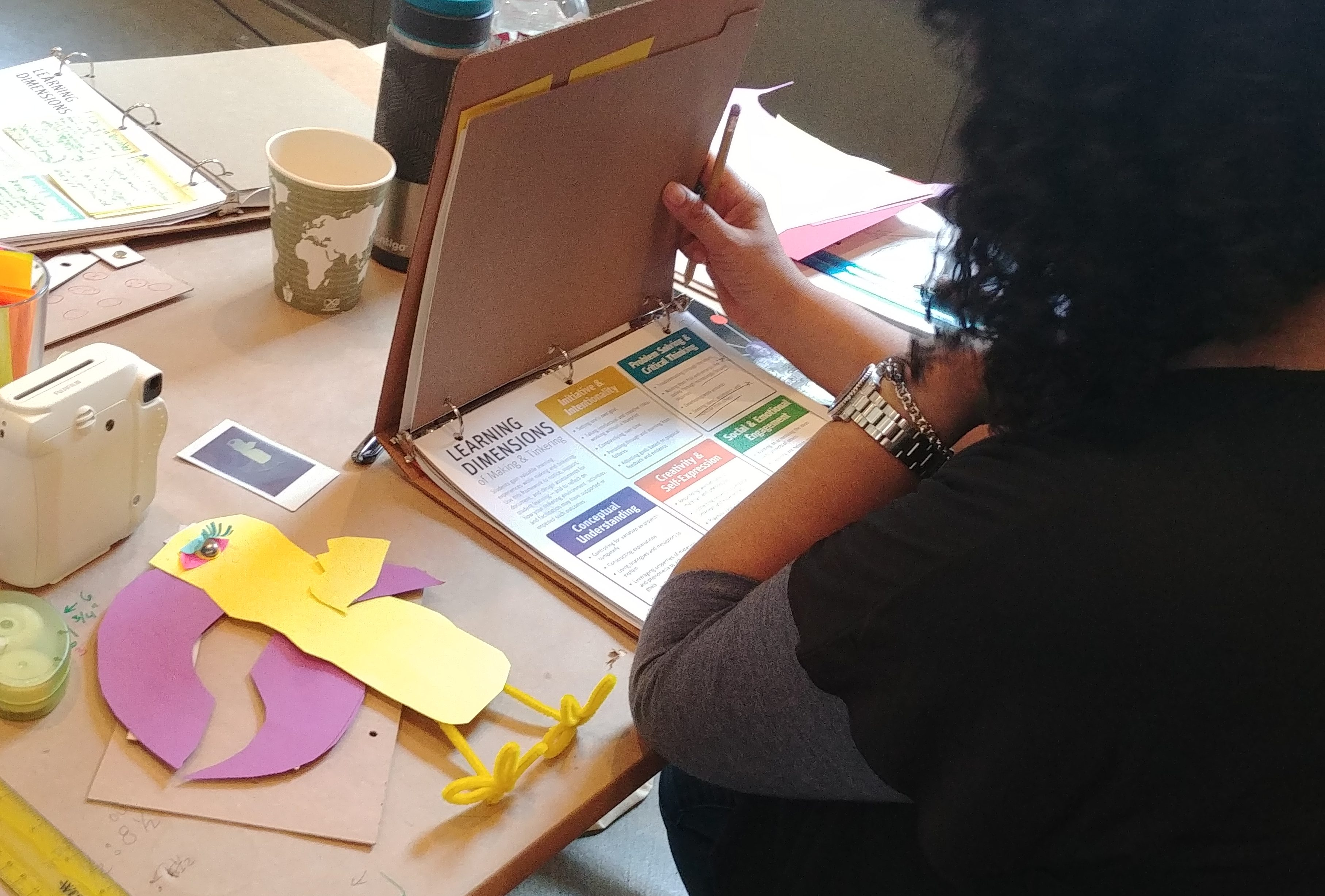 A workshop participant with curly, black hair looks at the learning dimensions of making and tinkering handout.