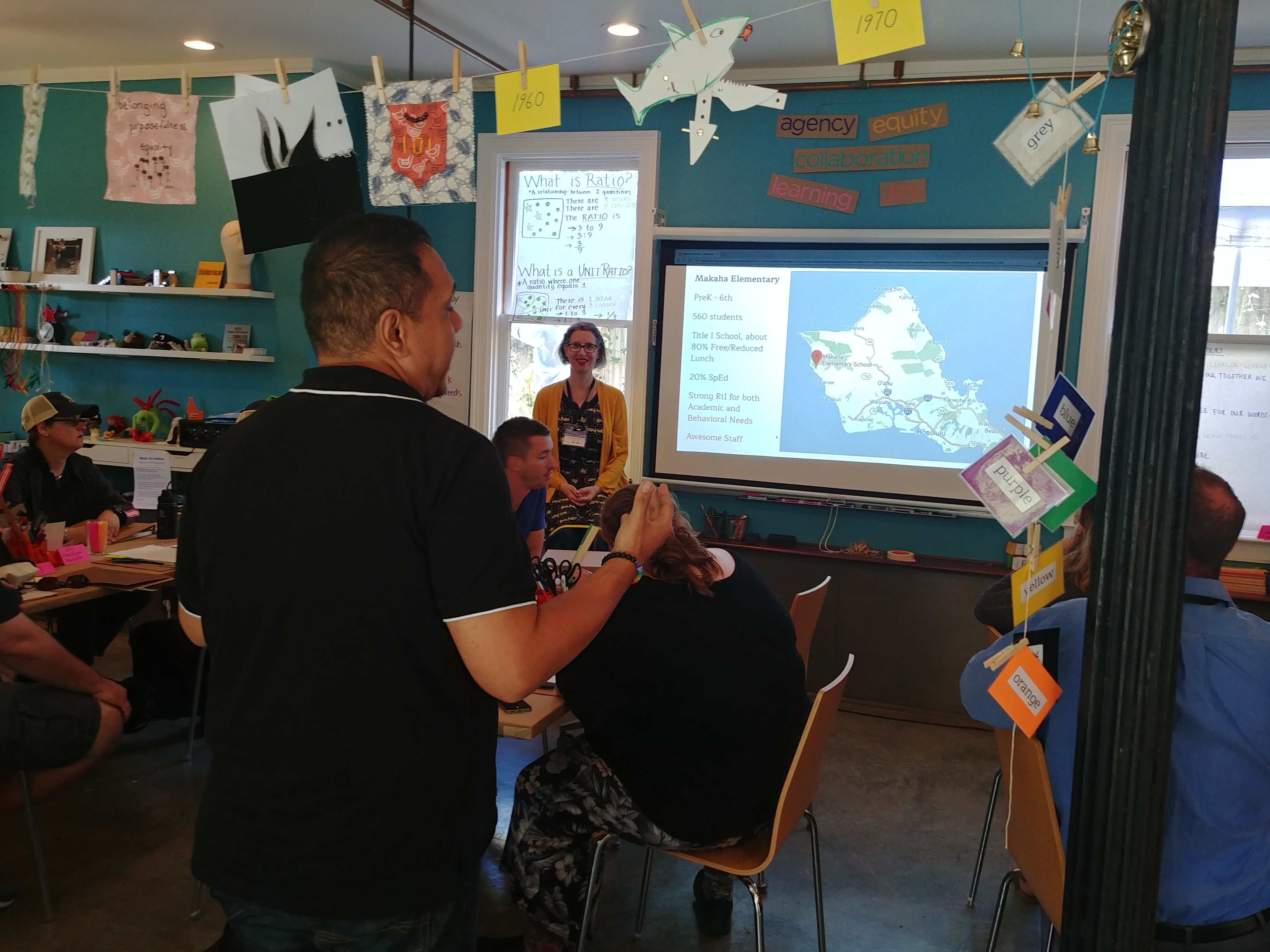 Two workshop participants give an ignite talk while a map of their home state is projected behind them.