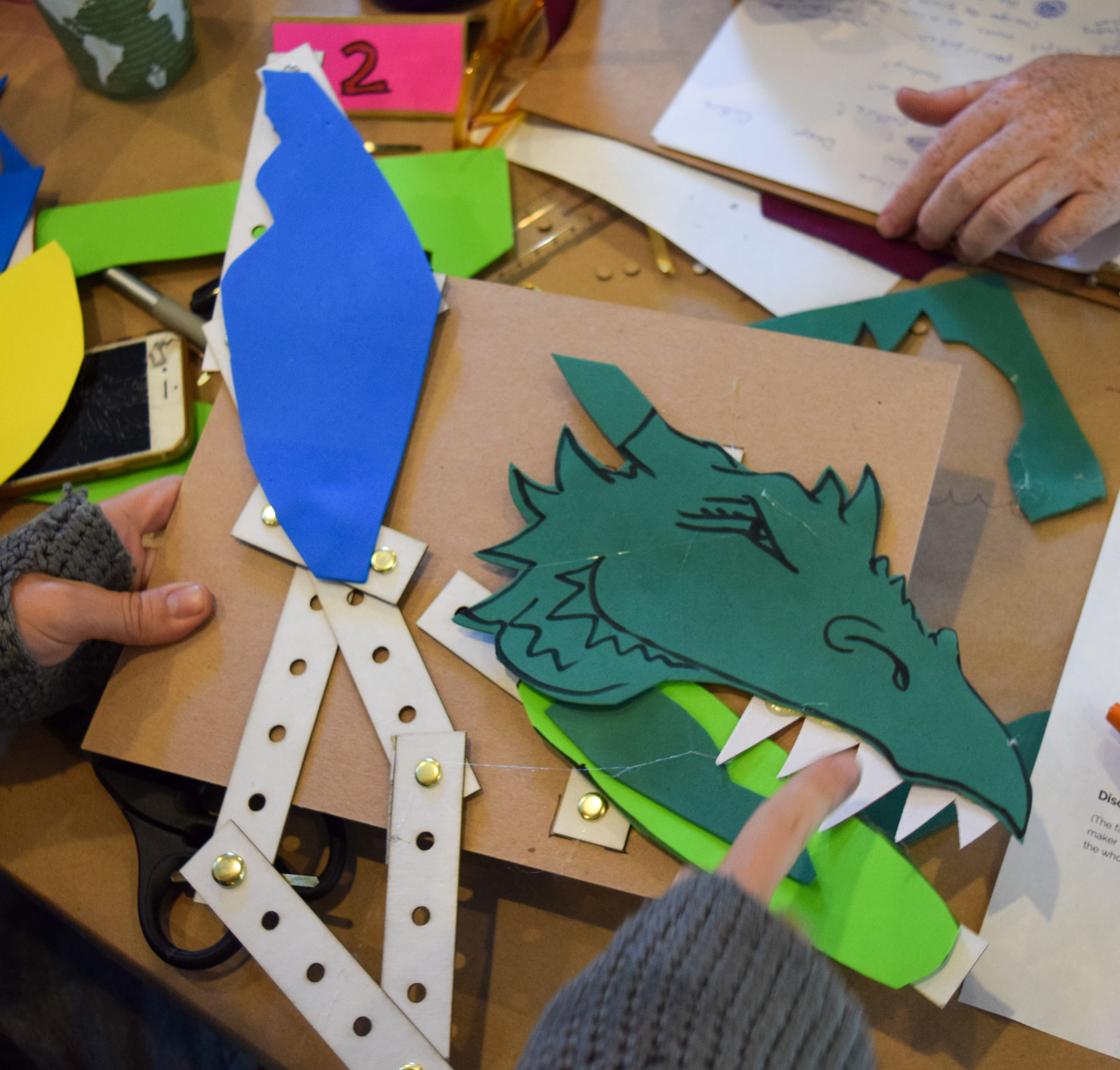 A cardboard linkage creature, a dragon. The dragon is made of green foam, with a blue wing, and sharp white teeth.