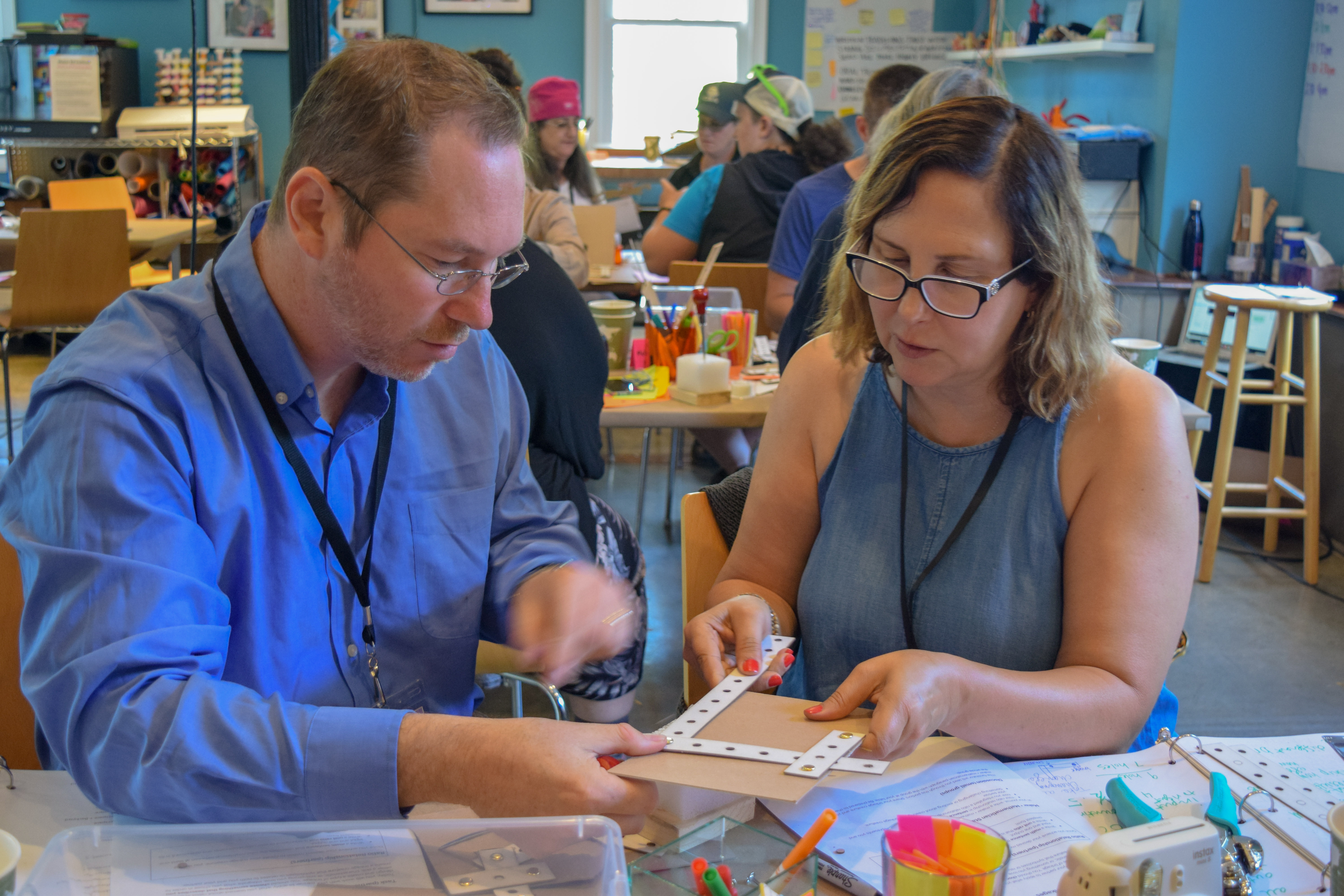 Two workshop participants, a man and a woman, examine a cardboard linkage they have created together.