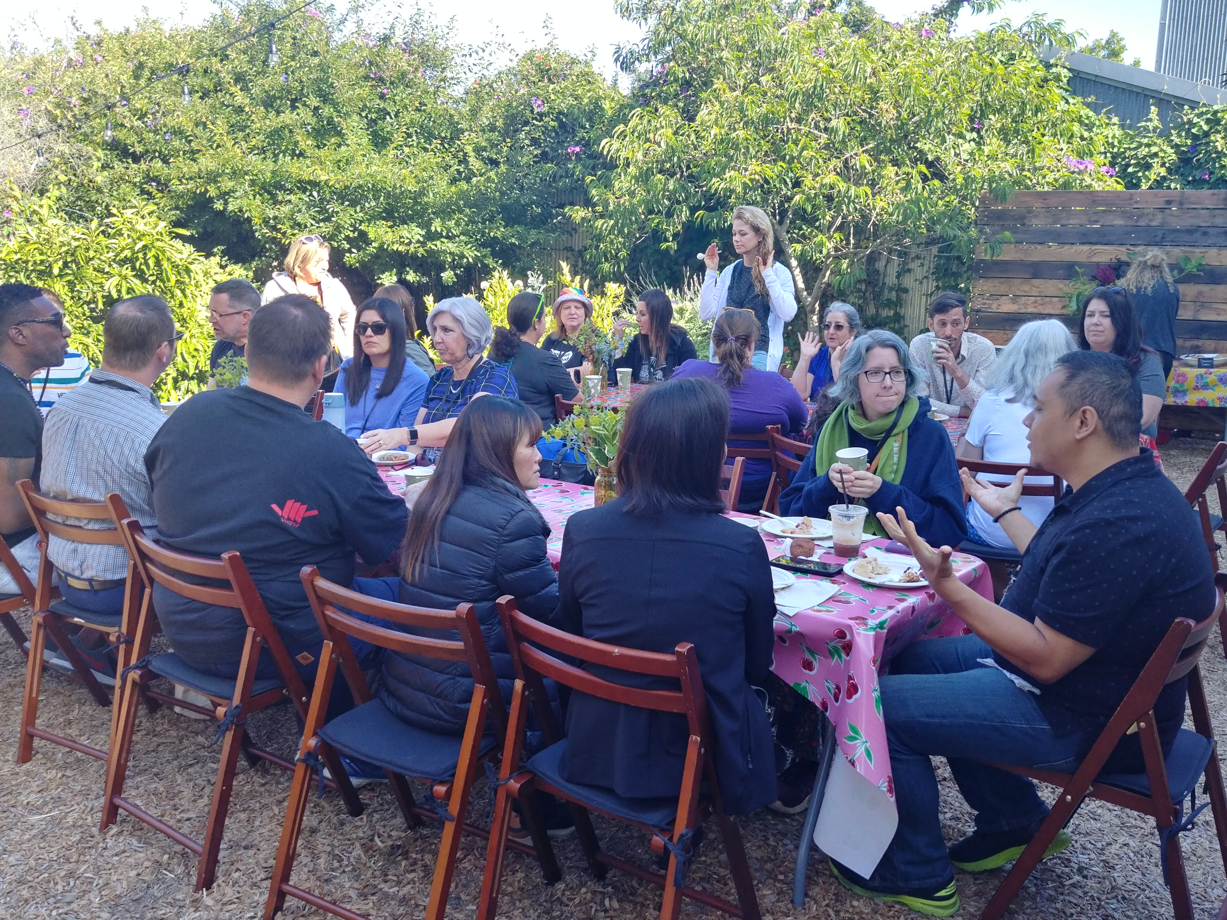 A large group of people sit and eat at long tables outside in a garden.