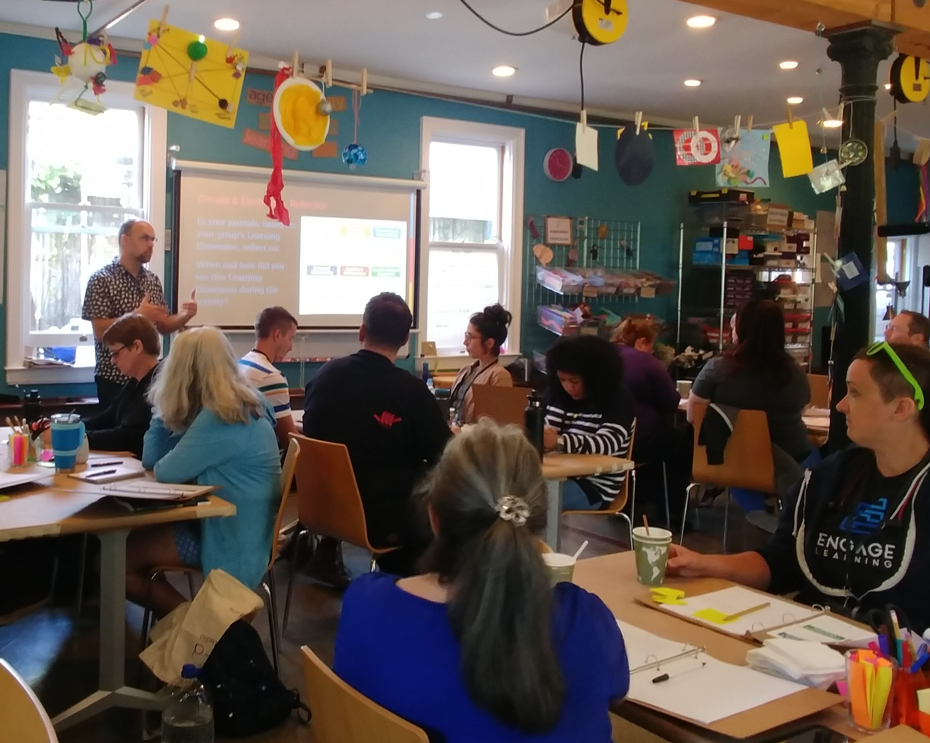 A wide group shot of 10 educators in the Maker Ed Community Studio makerspace