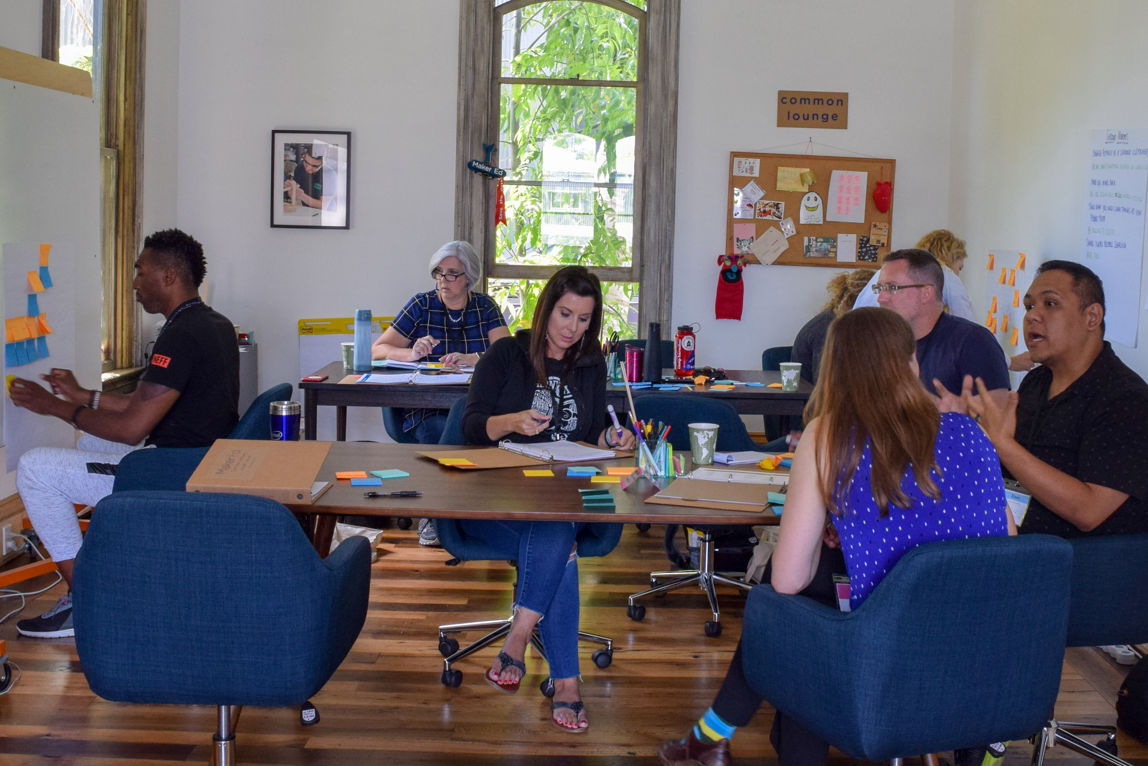A group shot of six workshop participants. Some attendees work independently while others talk in small groups of 2 or 3 people.