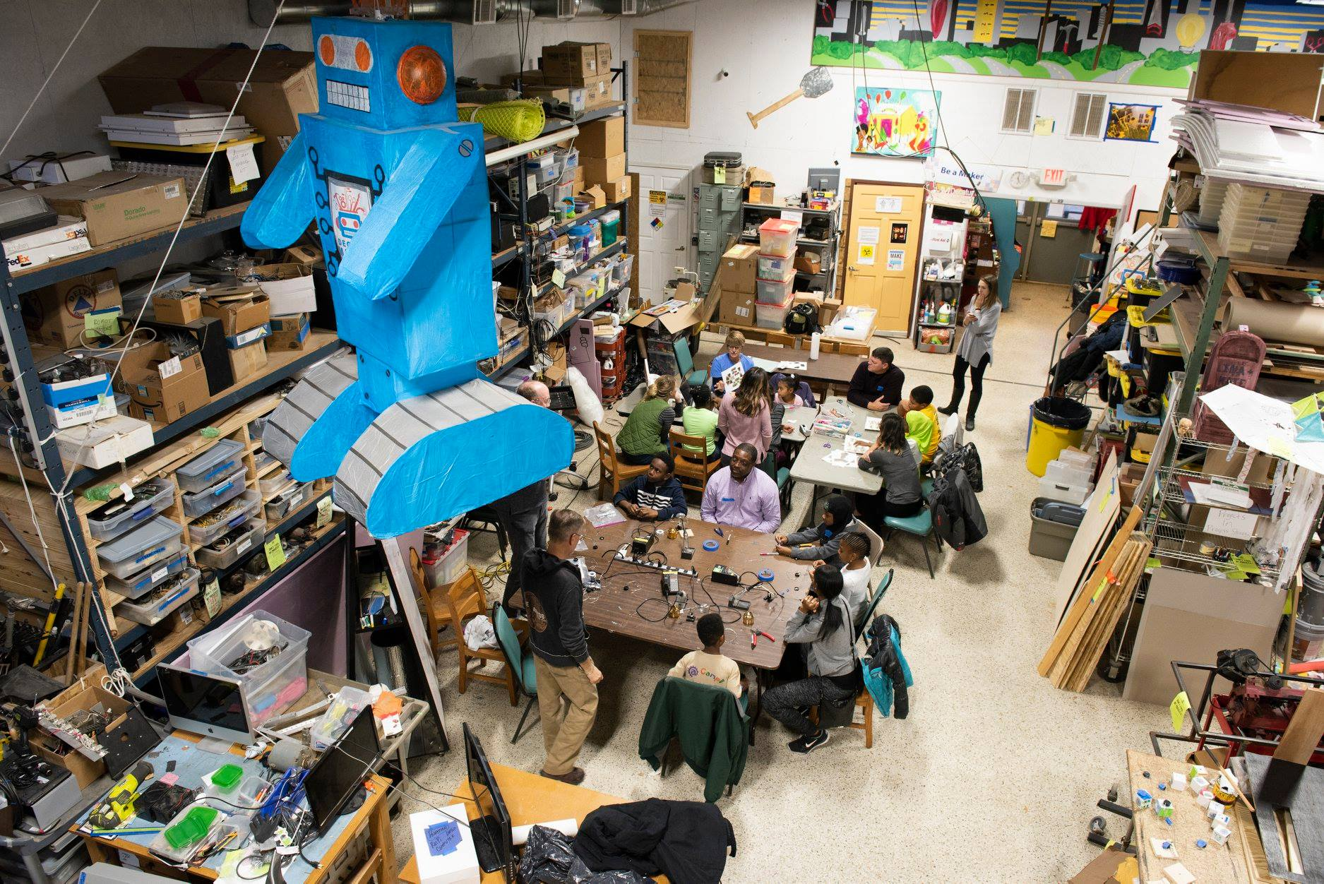 An overhead shot of Decatur Makers' space shows a large blue robot sculpture hanging from the ceiling, and several adults sitting in groups around tables.