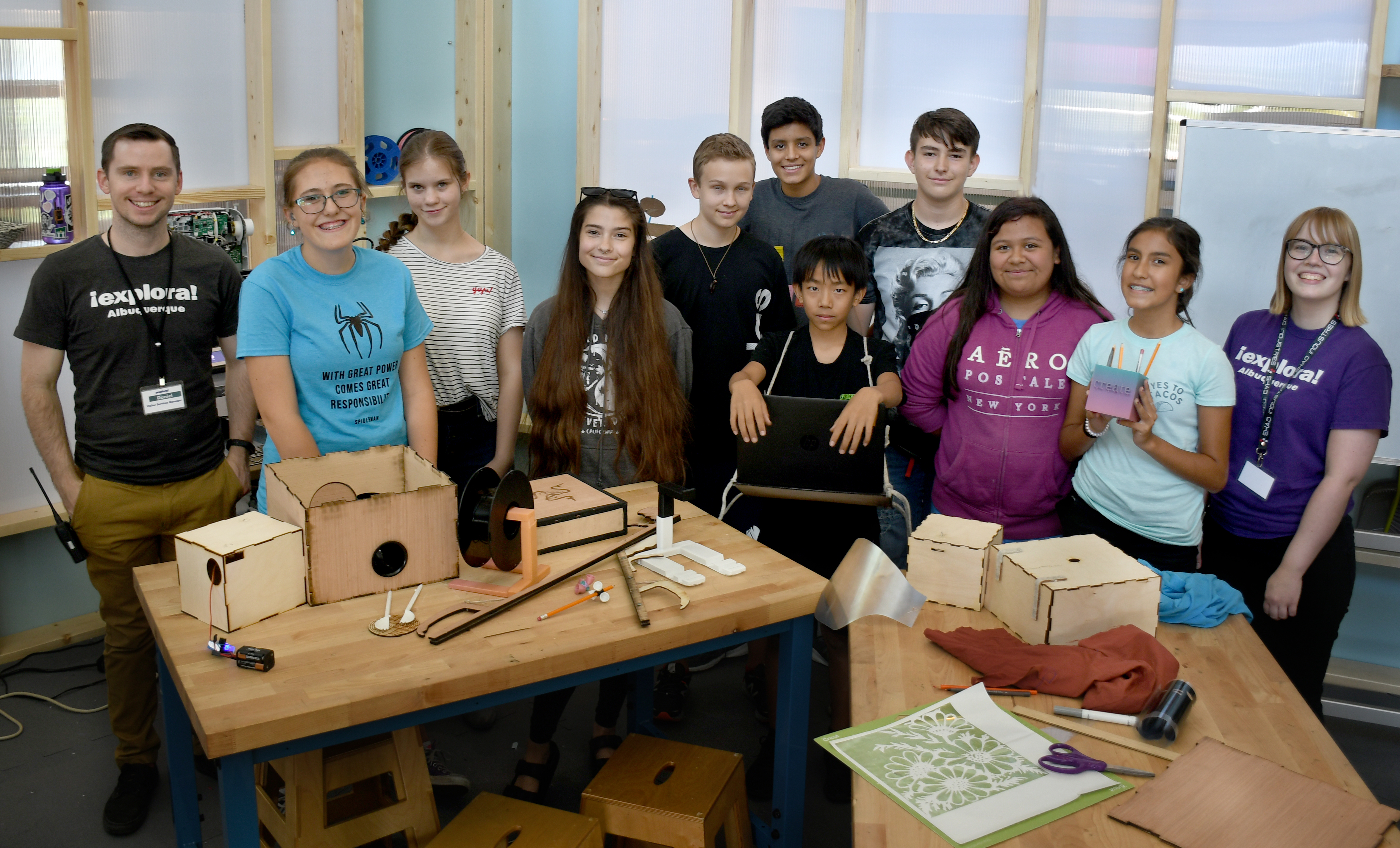 A group shot of several middle-school students proudly showing off their laser-cut woodworking projects.