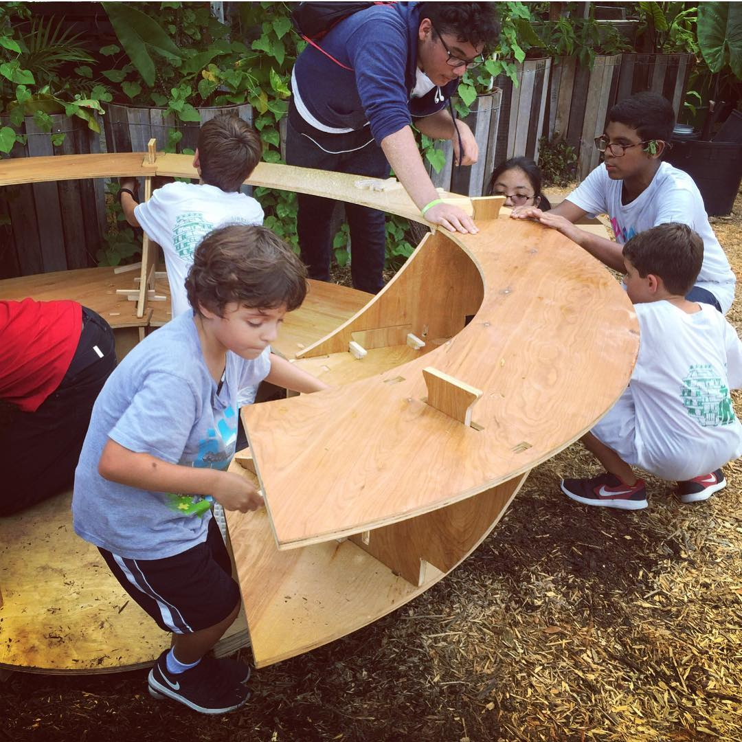 A group of 5 youth learners work on a woodworking project with an instructor.