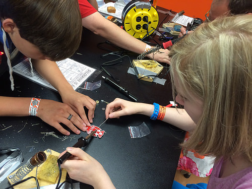 Two young students practice soldering together. A brown-haired youth on the left holds a plastic piece on the table while a blond-haired youth on the right holds the soldering iron and solder wire.