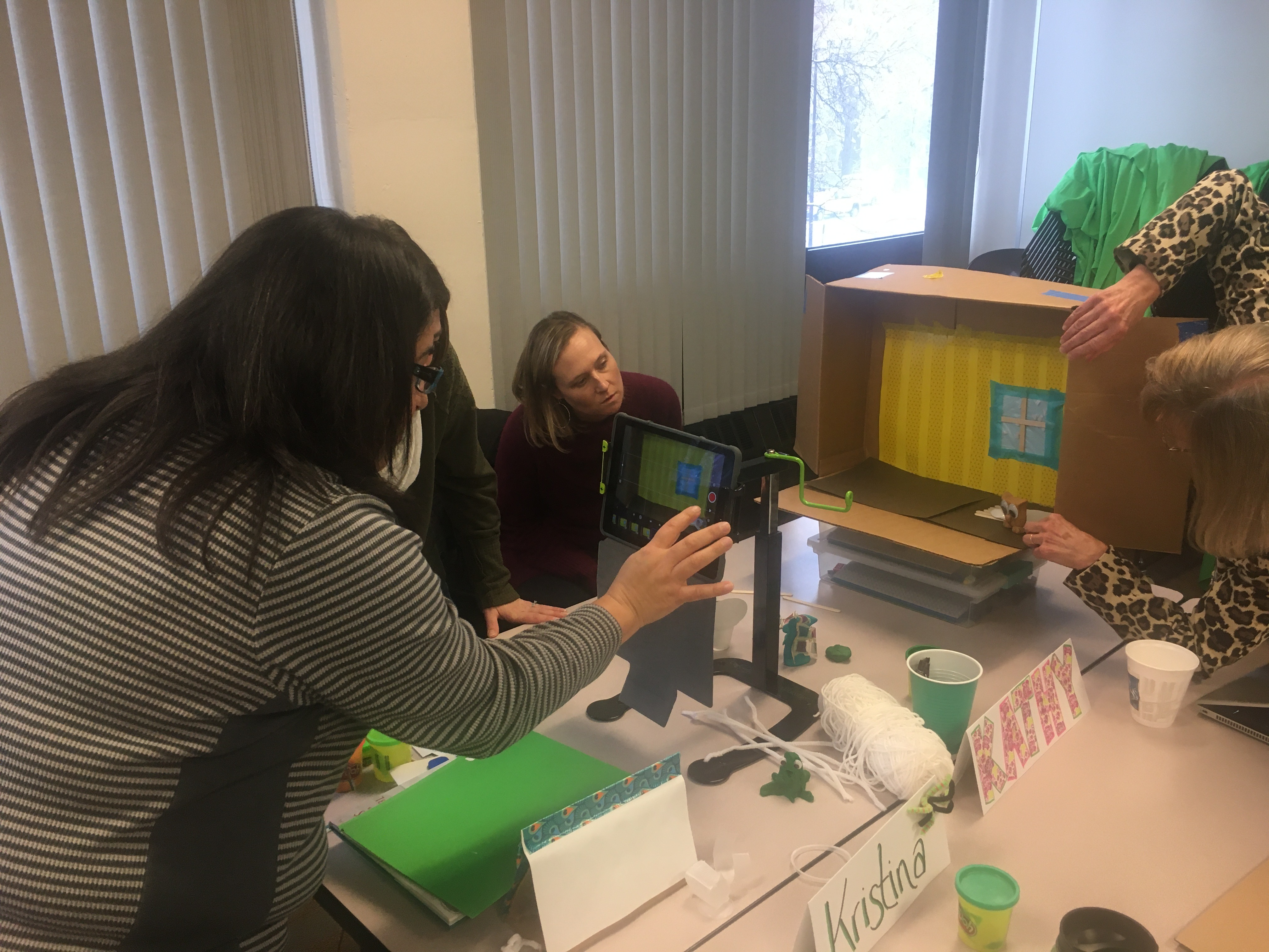 Four educators participate in a professional development workshop. They are learning how to document projects by taking photos of a diorama.