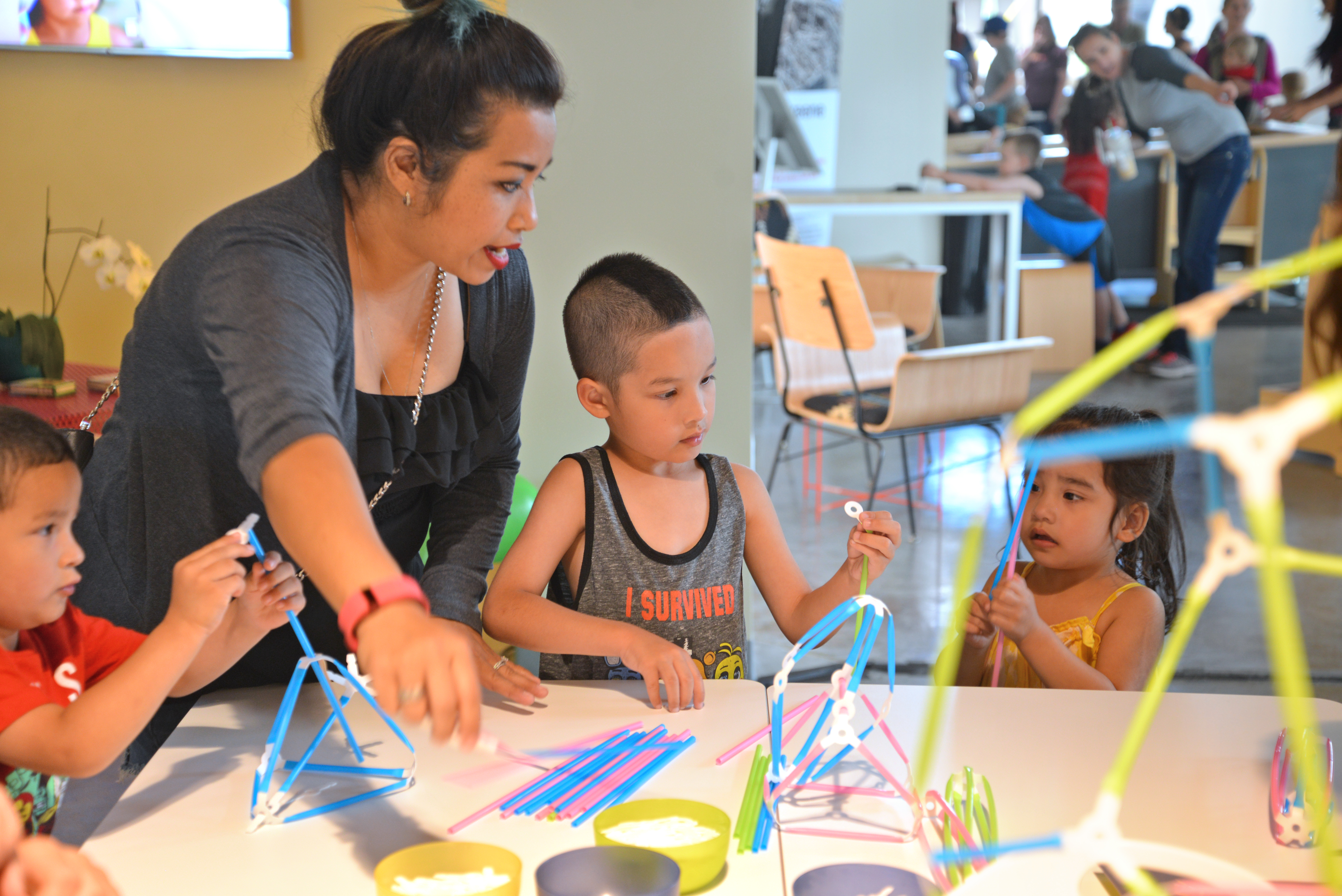 A woman leads 3 young children in a maker activity using straws and Strawbees