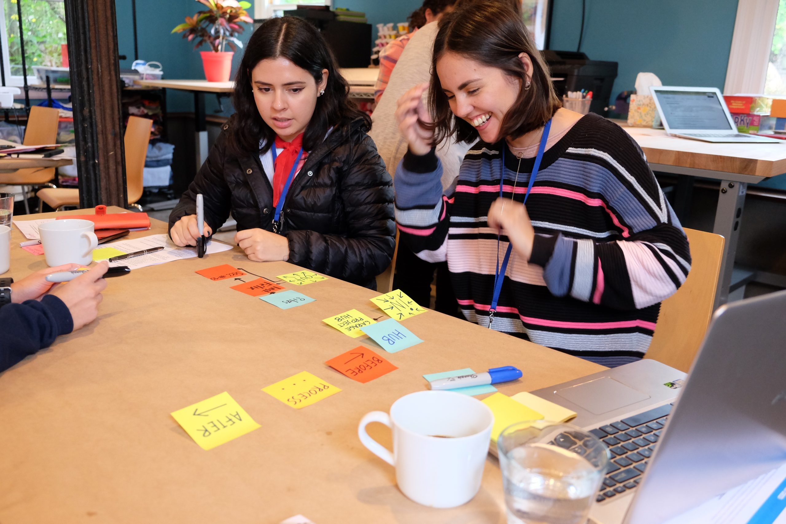 Two women sit at a table with many colorful post-it notes in front of them. One is writing something down and the other is smiling and laughing.
