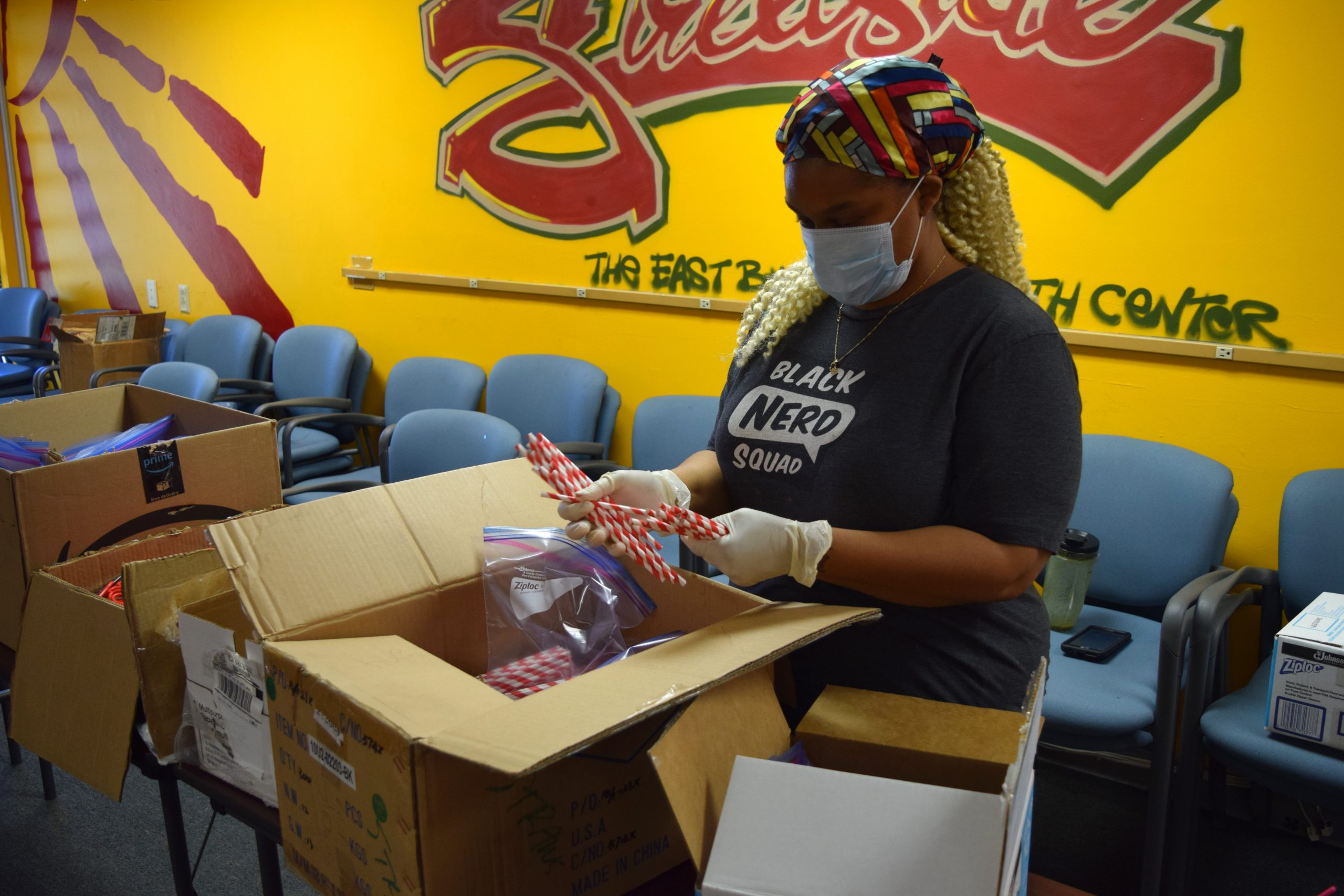 "A black woman wearing a colorful head wrap, a mask, and a shirt that says ""Black Nerd Squad"" helps pack paper straws into home maker kits."