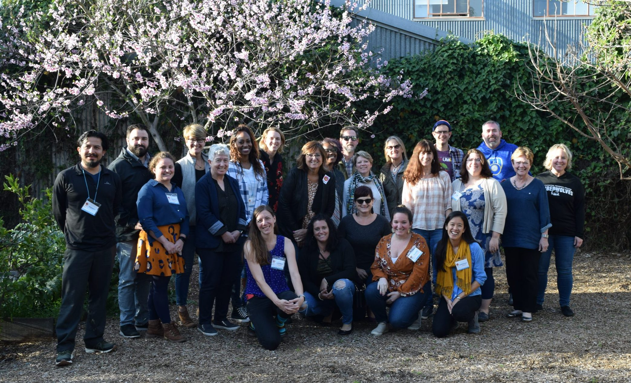 A group shot of Cohort 4 Hub representatives. They are standing outside in the back yard of the Maker Ed Community Studio