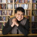 Kaustav Mitra sits in front of a book shelf. He is wearing a vest over a black sweater and smiling widely.