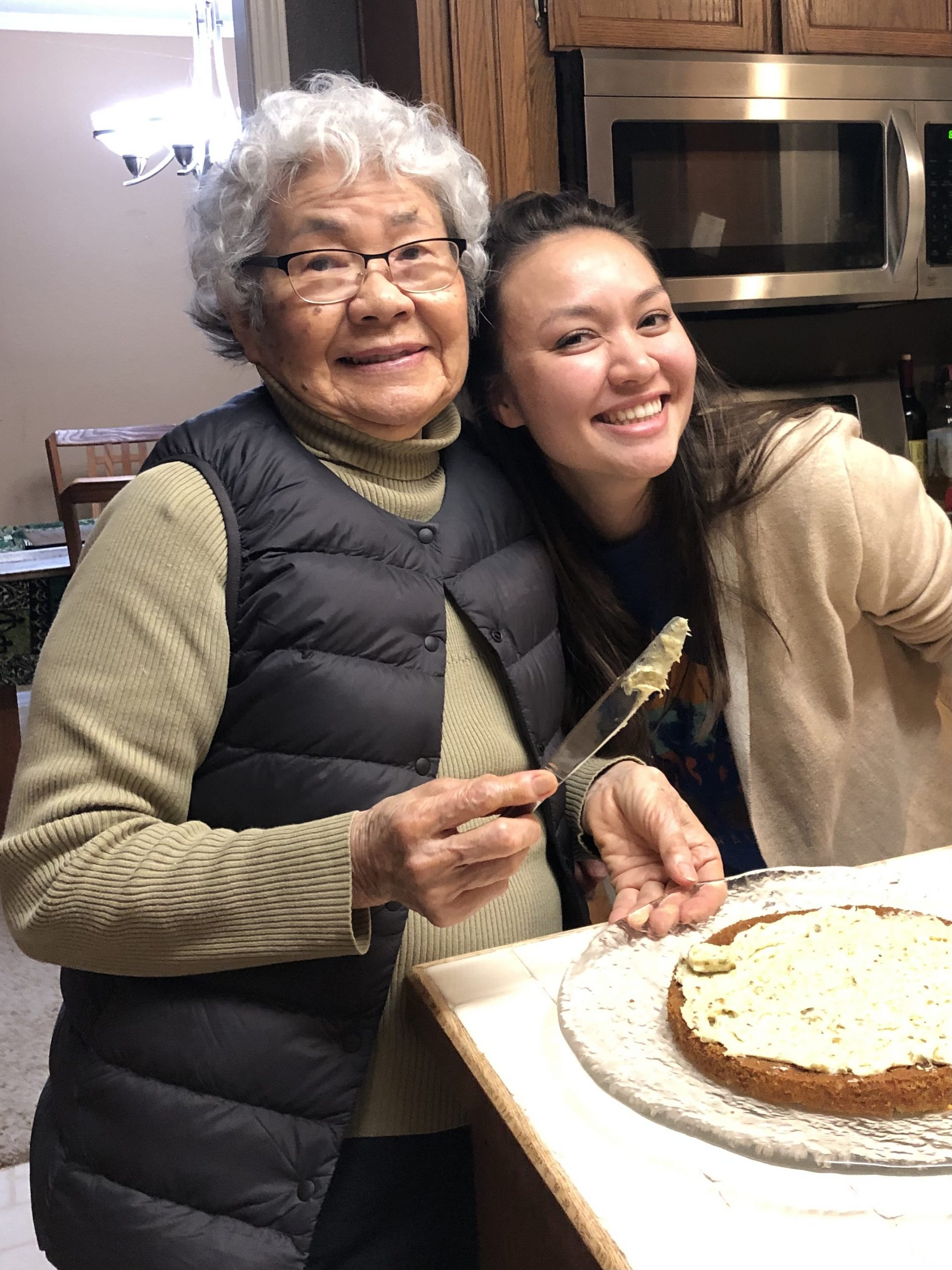 Annalise poses with her grandmother, an Asian woman with short, curly grey hair and glasses. They are making a cake together.