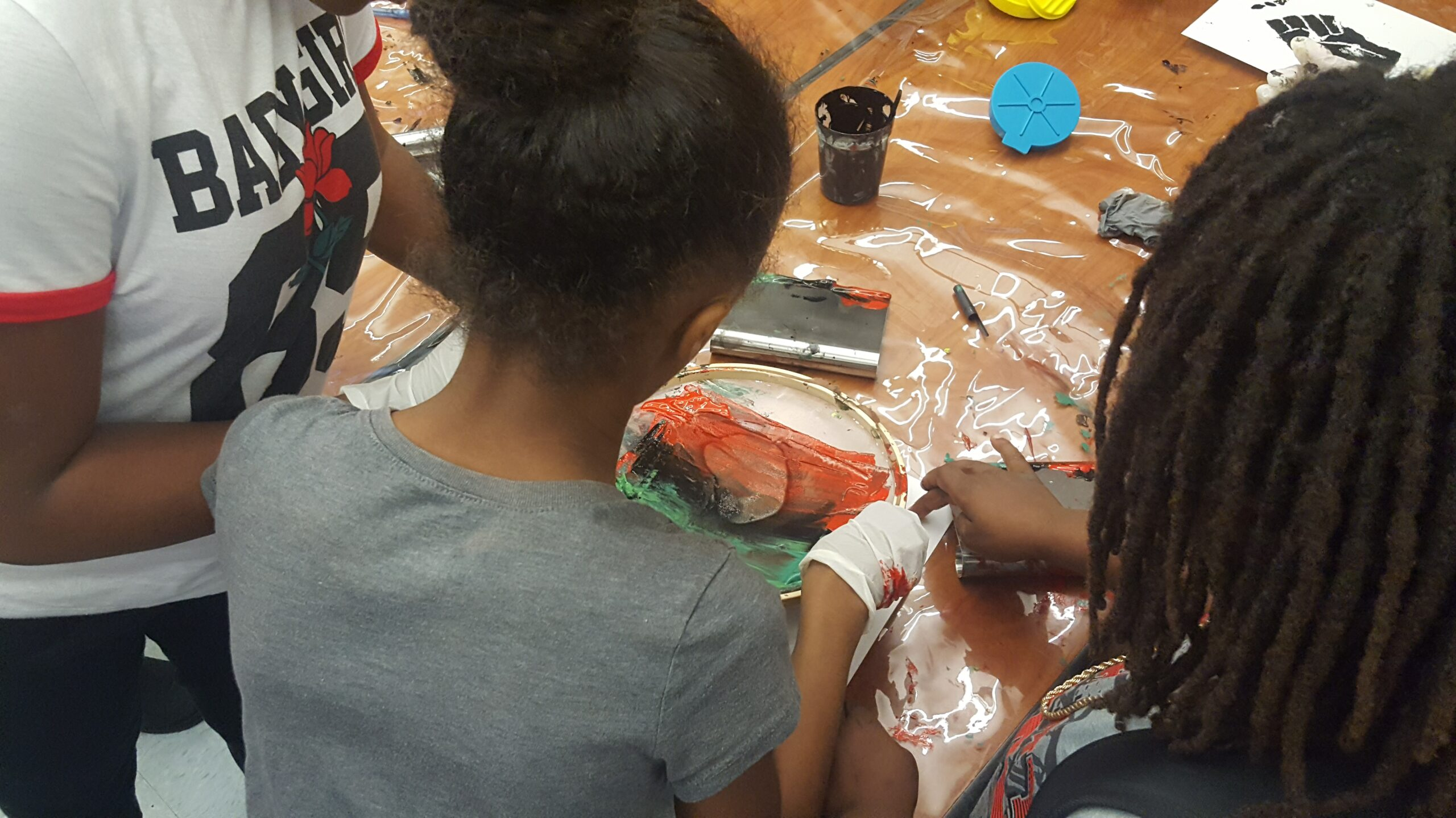 3 Black students at Grass Valley Elementary School in Oakland, CA participate in screenprinting together.