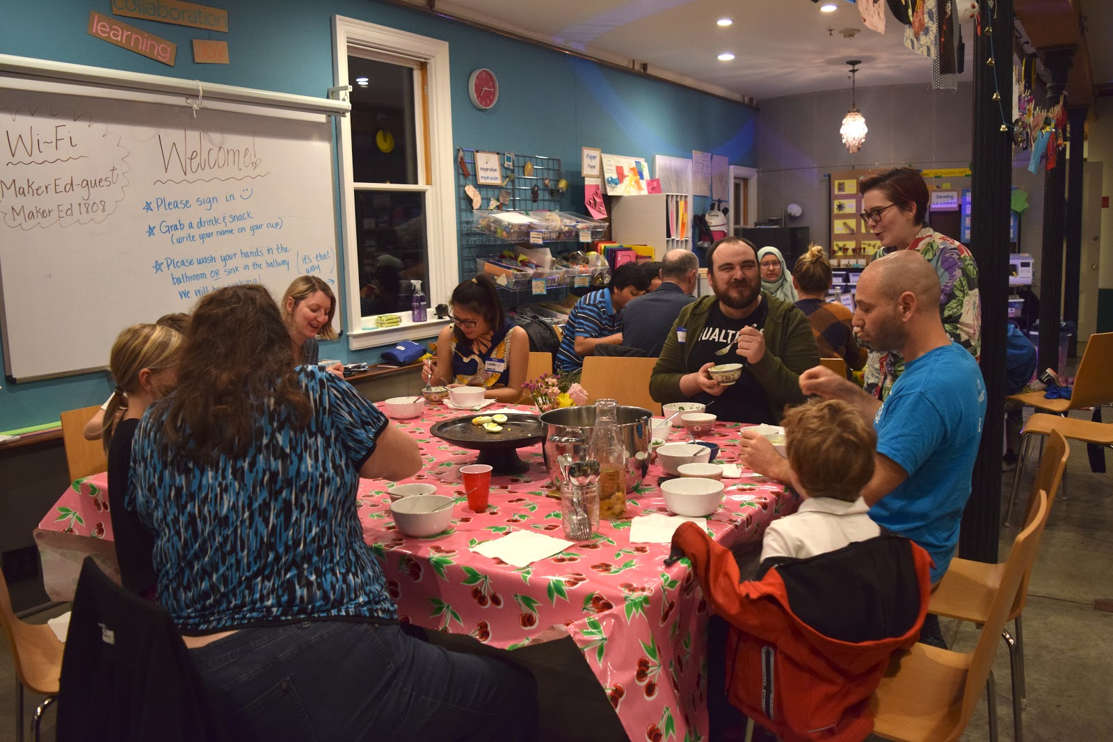 A group photograph at the Maker Ed Community Studio: meetup participants sit around a table smiling and eating together.