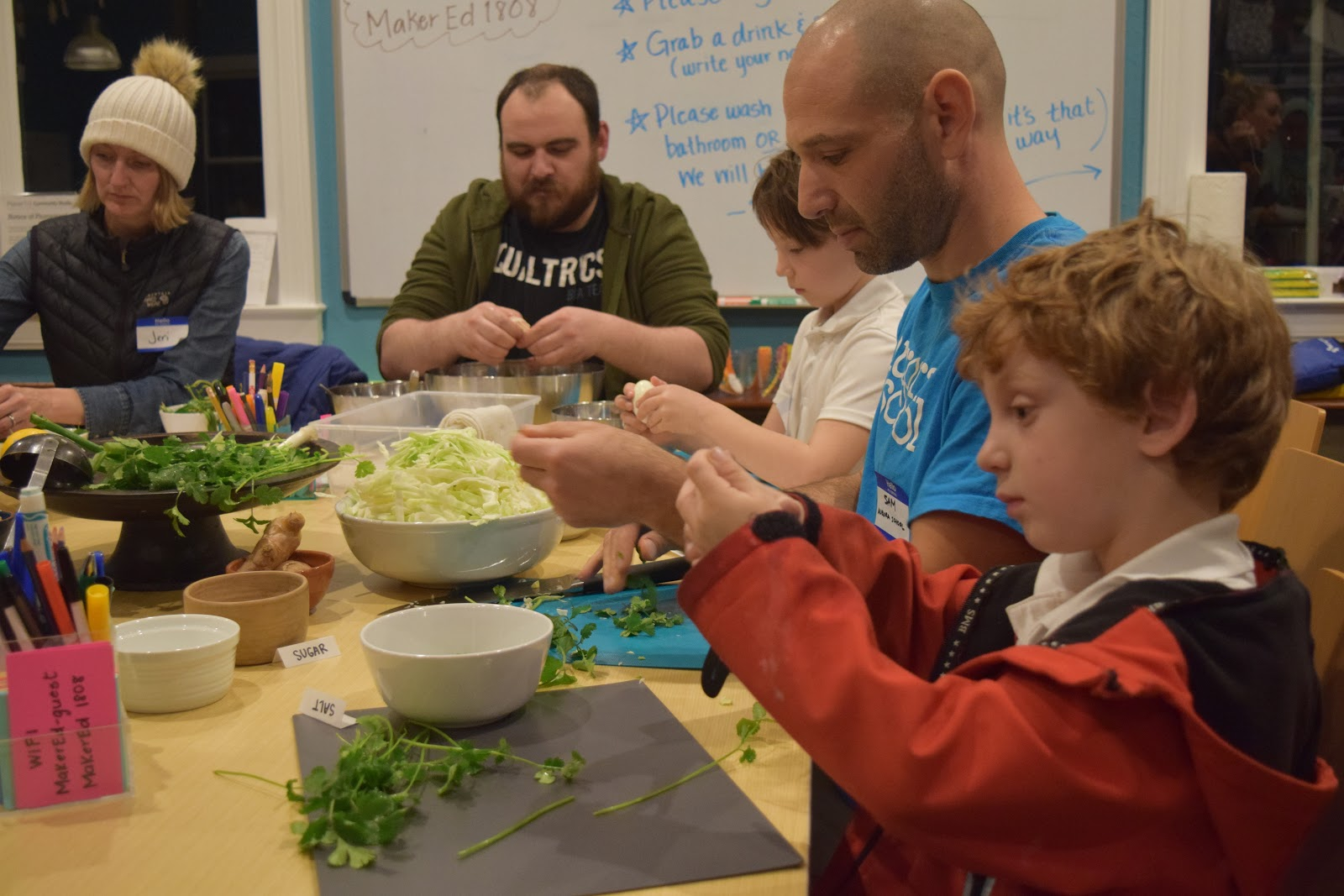 A parent and child prepare vegetables for cooking at the Maker Ed Community Studio.