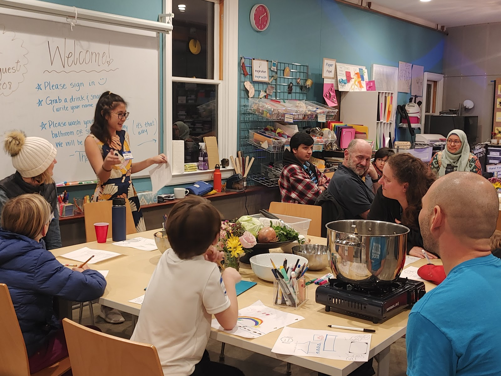 Linda, a Vietnamese-American staff member, shares a family recipe in the colorful Maker Ed Community Studio.