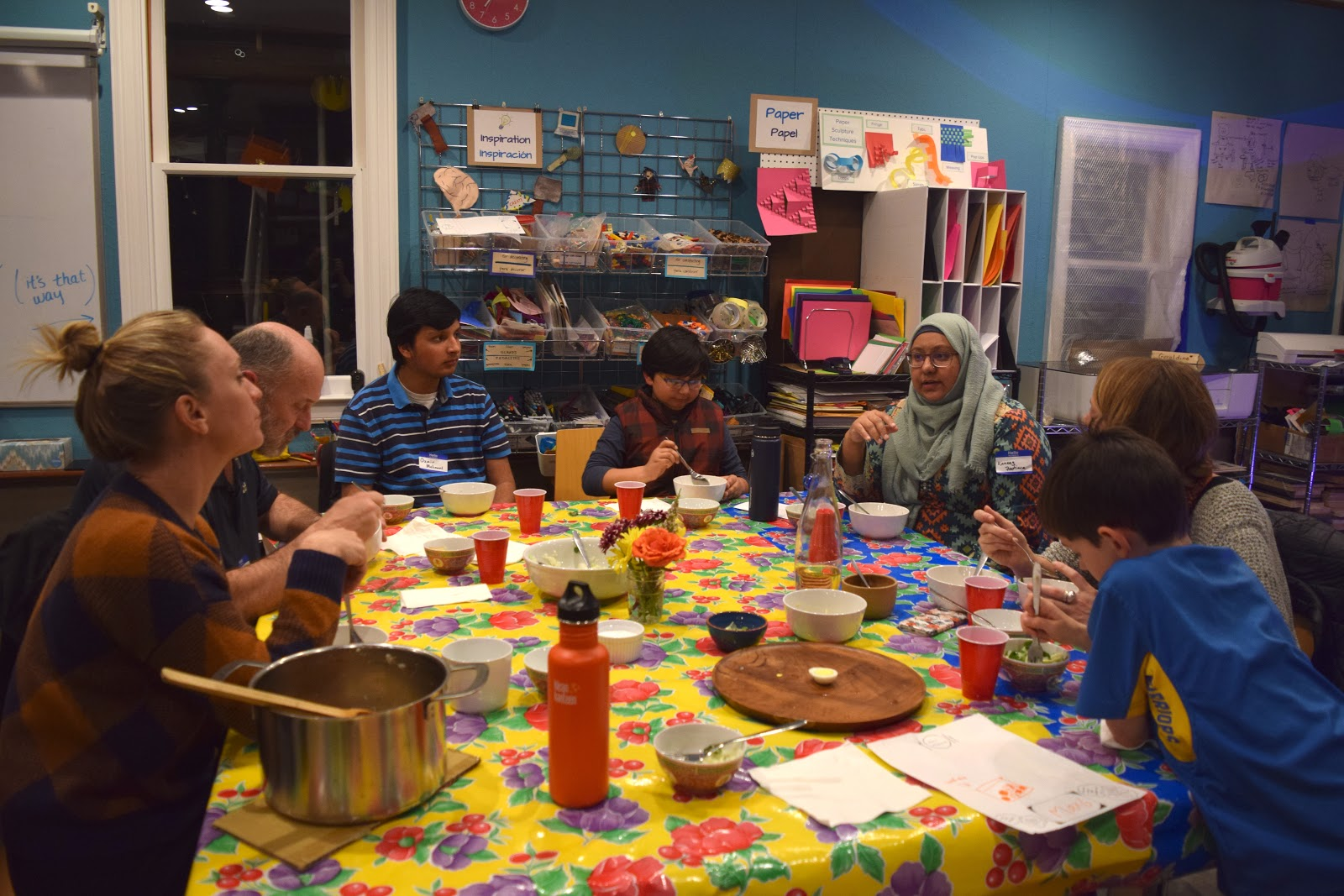 A photograph of a group of people enjoying a meal together at the Maker Ed Community Studio.