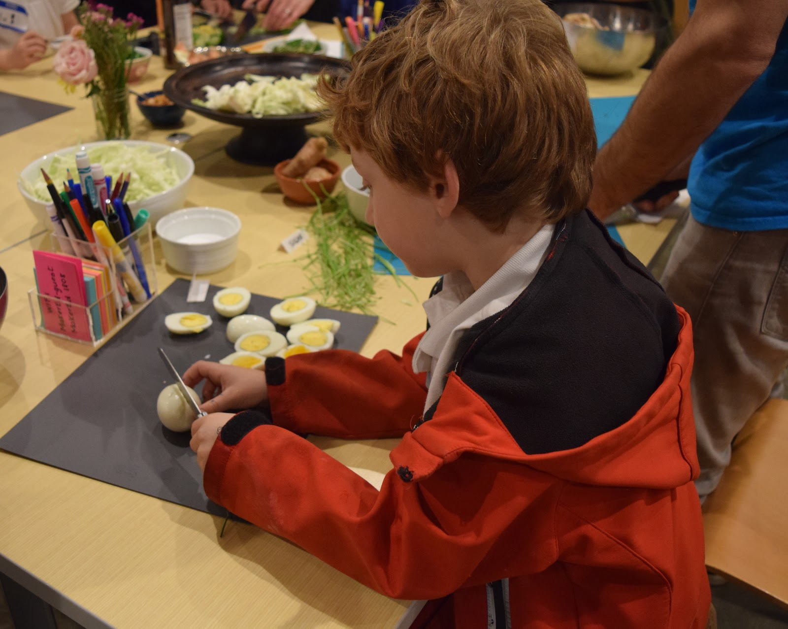 A photograph of a child, wearing a windbreaker, demonstrating the proper knife technique to cut hard-boiled eggs in half.