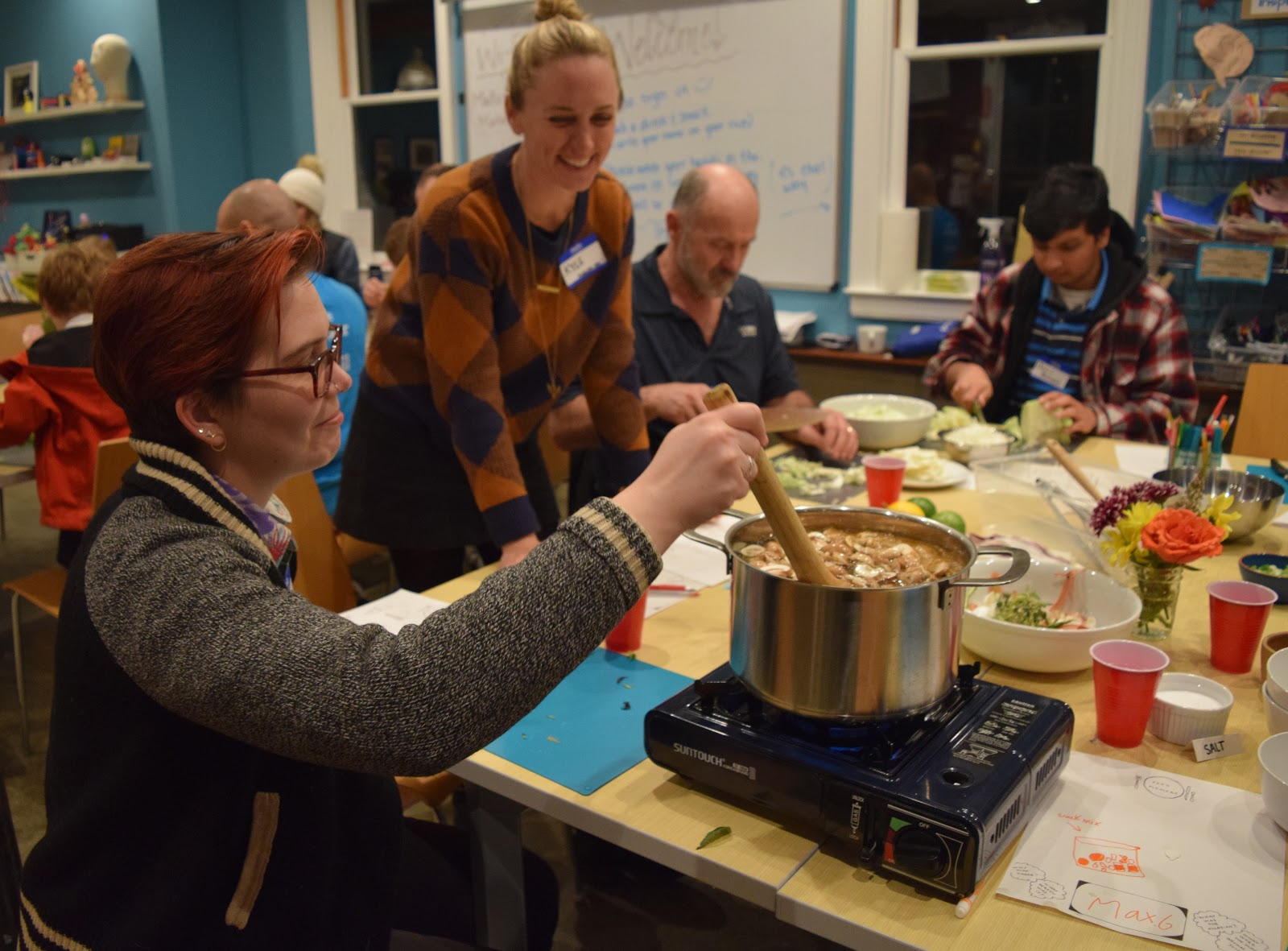 A photograph of meetup participants cooking together. One is stirring a pot and the other watches.