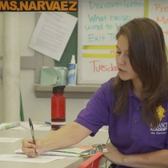 Jackie, a Latina woman, sits at the front of a classroom. She is wearing a school uniform polo shirt and writing something down.