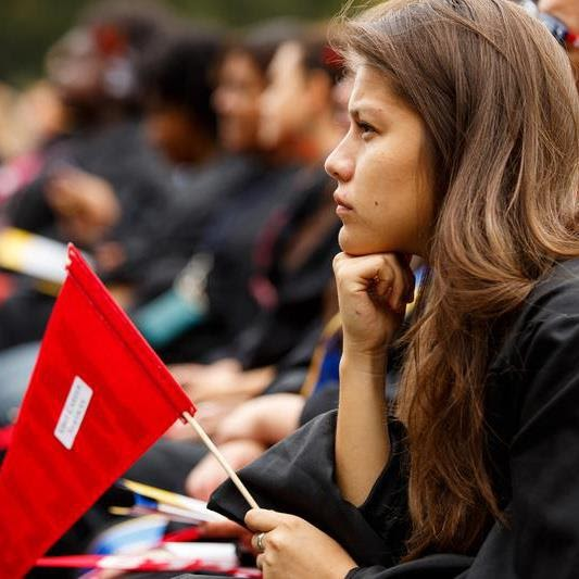 A photograph of Jackie Macy in profile - a Latina woman with long wavy hair wearing a black graduation gown and holding a red flag. She looks pensively away from the camera.